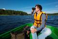 Man in the boat looks in the binoculars - PhotoDune Item for Sale