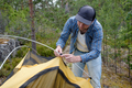 Male tourist making a tent at forest camp. - PhotoDune Item for Sale