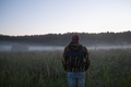 Man walking in a misty meadow hiking in the evening. - PhotoDune Item for Sale