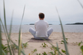 young man meditating at the sea. Rear view - PhotoDune Item for Sale