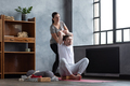 Man doing shoulders stretching. Female teacher helping him to stretch muscles. - PhotoDune Item for Sale