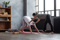 Yoga teacher or pilates instructor helping young man to stretch muscles - PhotoDune Item for Sale