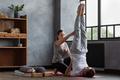 Yoga teacher helping a man to do Sarvangasana, the position of the Birch - PhotoDune Item for Sale