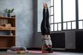 Woman practicing yoga near window in headstand exercise, salamba sirsasana - PhotoDune Item for Sale