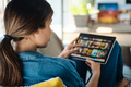 Woman Choosing Movie For Streaming On Tablet - PhotoDune Item for Sale