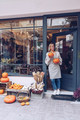 Smiling woman is holding pumpkins in front of her shop - PhotoDune Item for Sale