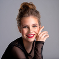 Young girl posing in the studio on a grey background. Happy caucasian girl smiling at camera. - PhotoDune Item for Sale
