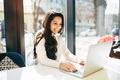 Brunette using laptop in cafe - PhotoDune Item for Sale