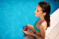 Woman relaxing and sun tanning by the swimming pool - PhotoDune Item for Sale