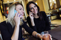 Two beautiful women talking on phone in cafe - PhotoDune Item for Sale
