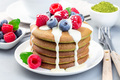 Matcha pancakes served with condensed milk, blueberry and raspberry on  white plate, horizontal - PhotoDune Item for Sale