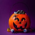 Jack-o-lantern bag full of candy on  dark purple background, square format - PhotoDune Item for Sale