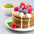 Matcha pancakes served with condensed milk, blueberry and raspberry on a white plate, square format - PhotoDune Item for Sale