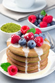 Matcha pancakes served with condensed milk, blueberry and raspberry on white plate, vertical - PhotoDune Item for Sale