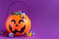 Jack-o-lantern bag full of liquorice candy on purple background with copy space,  horizontal - PhotoDune Item for Sale