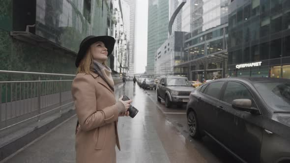 Female tourist holding camera outdoors in a modern city street