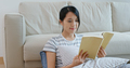 Woman read book and sit on sofa at home - PhotoDune Item for Sale