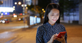 Woman use of mobile phone online in city at night - PhotoDune Item for Sale