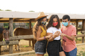 Friends Having Fun Using a Smart Phone in a Ranch with Protective Masks - PhotoDune Item for Sale