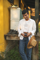 Placeit - A Young Man Resting Near Old Shoes and Using Smartphone for Messaging - PhotoDune Item for Sale