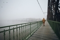 Lonely man walking on bridge against city in mysterious fog - PhotoDune Item for Sale