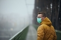 Lonely man wearing face mask against city in fog - PhotoDune Item for Sale