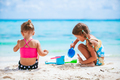 Two little happy girls have a lot of fun at tropical beach playing together - PhotoDune Item for Sale