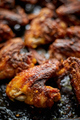 Grilled chicken wings in spices in black metal baking tray on stone table. Top view - PhotoDune Item for Sale