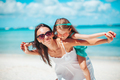 Beautiful mother and daughter at the beach enjoying summer vacation - PhotoDune Item for Sale