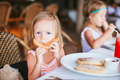 Adorable little girl having breakfast at outdoor cafe - PhotoDune Item for Sale