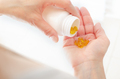 Caucasian female hands with yellow pills and medicine bottle closeup - PhotoDune Item for Sale