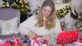 Young blond woman wrapping xmas gift box sitting next to table in living room - PhotoDune Item for Sale