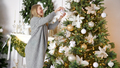 Happy young blond woman decorating christmas tree with ball at her home - PhotoDune Item for Sale