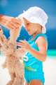 Little girl at tropical white beach making sand castle - PhotoDune Item for Sale