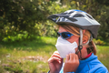 Shallow focus of a female cyclist wearing a helmet, sunglasses, and a facemask - COVID-19 - PhotoDune Item for Sale