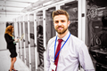 Smiling technician standing in a server room - PhotoDune Item for Sale