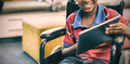 Disabled schoolboy on wheelchair using digital tablet in library - PhotoDune Item for Sale