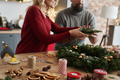Couple making Christmas wreath at table full of decorations - PhotoDune Item for Sale