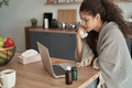 Sick woman sitting  in front of the laptop at home - PhotoDune Item for Sale