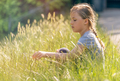 Little girl sitting in the high grass in a park - PhotoDune Item for Sale
