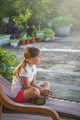 Cute Caucasian girl resting on a reclining wooden chair - PhotoDune Item for Sale