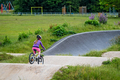 Young girl riding on her bicycle on a dirt race track - PhotoDune Item for Sale