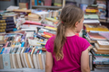Girl looking at books for sale on a street market in China - PhotoDune Item for Sale