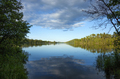 Calm blue northern Minnesota lake and treeline on a sunny evening - PhotoDune Item for Sale