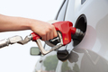Isolated arm and hand of a young man pumping gas into a car - PhotoDune Item for Sale