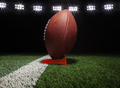 Low angle view of a football on a tee on black background under lights - PhotoDune Item for Sale