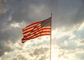 Back lit American flag waving under clouds with sun rays at sunset - PhotoDune Item for Sale