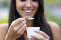 Beautiful young woman smiling while eating an ice cream standing in the street. - PhotoDune Item for Sale