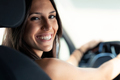 Beautiful young woman driving a car while smiling to the camera. - PhotoDune Item for Sale