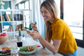 Smiling woman eating healthy food while using her mobile phone at home. - PhotoDune Item for Sale